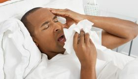 A sick man sneezing into tissues while lying in bed