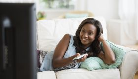 Black woman watching television on sofa