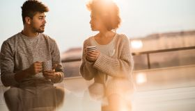 Young black couple talking to each other during coffee time.