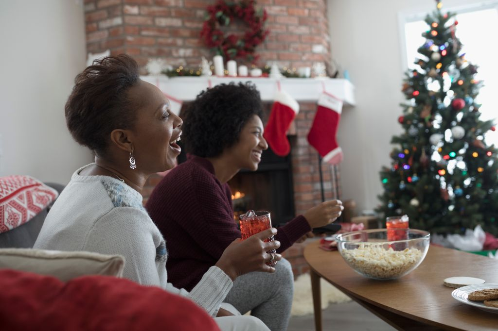 Mother and daughter watching TV, eating popcorn in Christmas living room