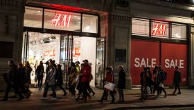 People walk past a 'sale' advertisement from an H&M store on...