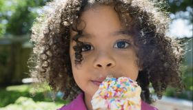 Close up portrait girl eating ice cream cone with sprinkles in sunny backyard