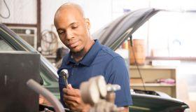 African descent mechanic working in auto repair shop.