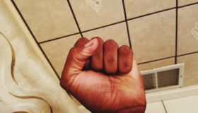 Cropped Hand Clenching Fist Against Ceiling
