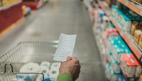 Close-up of a man holding shopping list in the supermarket