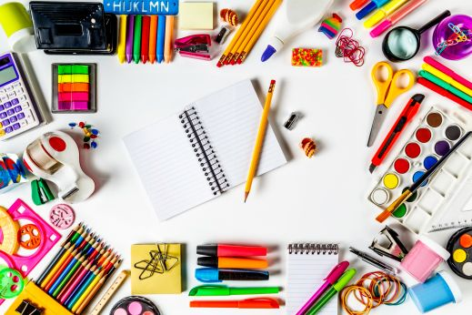 Overhead shot of back to school office supplies on white background with paper note book into frame.