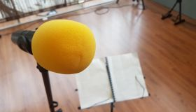 Close-Up Of Yellow Microphone By Sheet Music At Recording Studio