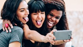 Three girl friends making funny faces for a selfie with cell phone