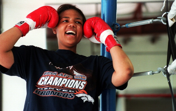 Boxer Freeda Foreman, daughter of former heaveyweight champion George Foreman, jokes with her trainer while posing for a portrait at America Presents Gym in Denver.