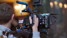 Young male video cameraman, photographer, shoots video or takes a photo on the camera.