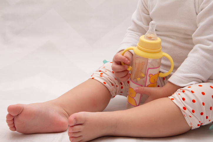 Low Section Of Baby Holding Milk Bottle On Bed At Home