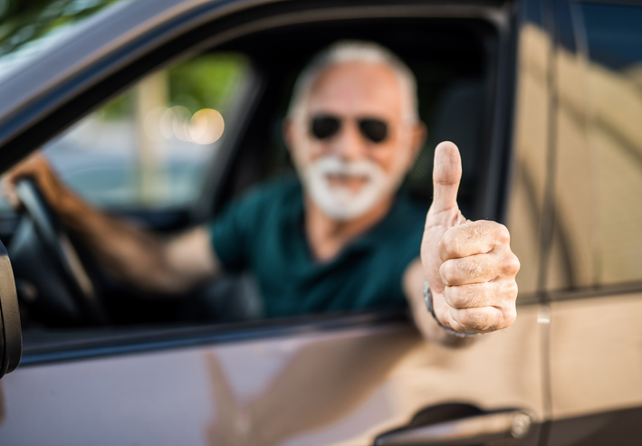 Senior man in car showing thumb up focus on foreground.