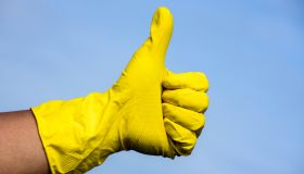 Hand in yellow protective glove showing thumbs up sign