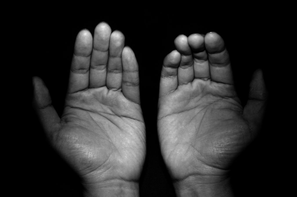 Close-Up Of Hands Against Black Background