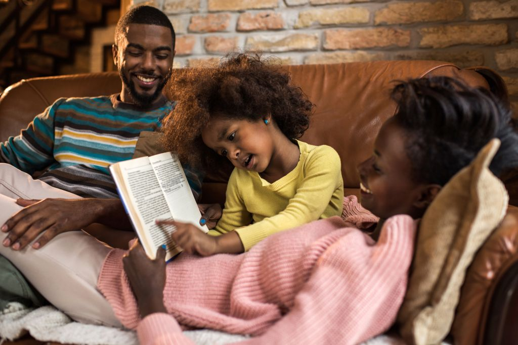 Little African American girl reading a book to her parents.