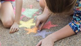 Sisters Doing Chalk Art On Driveway
