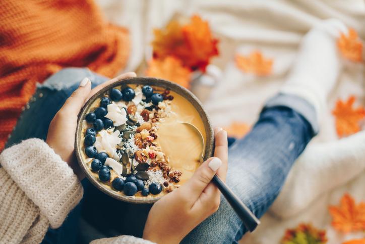 Woman holding a pumpkin smoothie bowl - Autumn concept