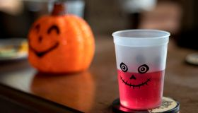 Red Halloween drink in cup on table with pumpkin